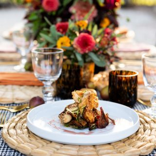 A dinner plating with a bouquet set out behind