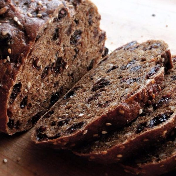 A close up of a loaf of pumpernickel raisin bread where it is sliced. Raisins and sesame seeds are visible.